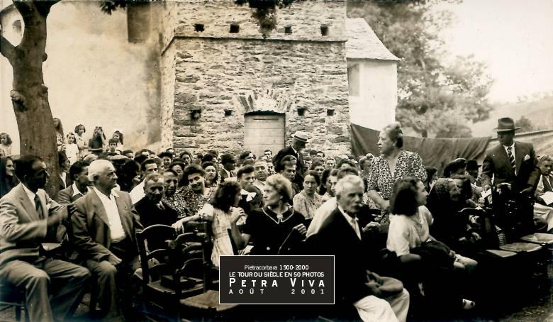 1933. Spectacle sur la place de l'église. C'est un moment de fête : les familles se rassemblent pour voir jouer les jeunes. Chacun amène sa chaise. De simples toiles séparent les spectateurs des coulisses et de la scène. L'ambiance est bon enfant. Collection Paul Franceschi.