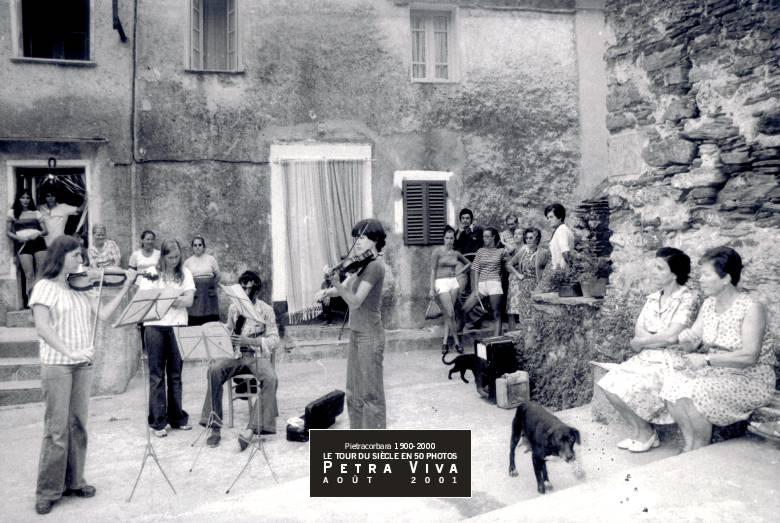 1977. Concerts au village. Ils se déroulent dans plusieurs hameaux. Ici, de jeunes musiciens répètent sur la piazza Là à Curtina, une oeuvre qui sera rejouée, le soir, dans l'église paroissiale. Observez le public des permanents et des vacanciers qui profite de ce moment hors du commun. Collection Dominique Antoni.