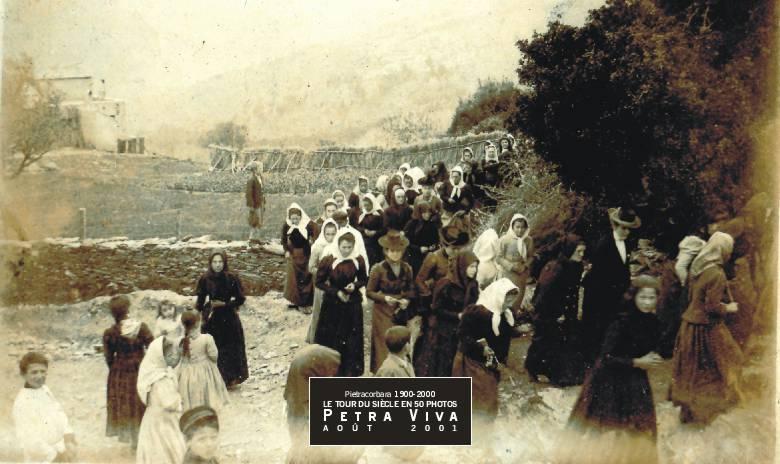 1916. Procession du Vendredi Saint à Lapedina suttana sur le chemin de la Croce. Beaucoup de jeunes femmes sont déjà en noir. S'agit-il des deuils de la guerre ? Un enfant est monté sur la murette pour voir passer le cortège. Observez, au fond, la haie en bruyère séchée. Un façon de limiter les dégâts du libecciu. Collection Simone Giorgi.