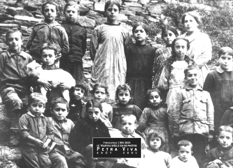 1915. Classe à Lapedina. L'une des deux écoles du village, installée à Lapedina suprana. A cette date, elle compte une vingtaine d'enfants. On y trouve des tous petits et des plus grands. Observez le garçonnet (François Guiliani - de Mathieu) qui tient un agneau dans ses bras. Collection Félix Giuliani.