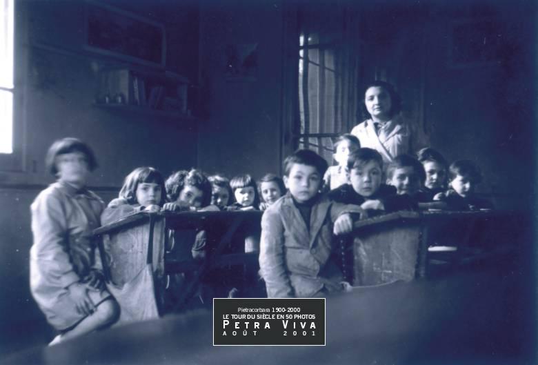1949. Classe de l'après-guerre. Ils sont douze enfants sérieux, sans sourires. Ils sont comme accrochés à leur bureau de bois, les uns contre les autres. La lumière est rare et oblique, elle ne parvient que d'une seule fenêtre. C'est une photo à la Doisneau, belle par son austère simplicité. Collection Maurice Havel.
