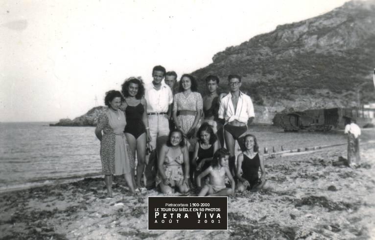 1946. Une journée à la plage. Voilà une bande qui aime la vie ! Observez la masse sombre de la péniche allemande pilonnée, trois ans plus tôt, par l'aviation américaine ainsi que les restes d'un ponton de bois. Collection Nanou Graziani.