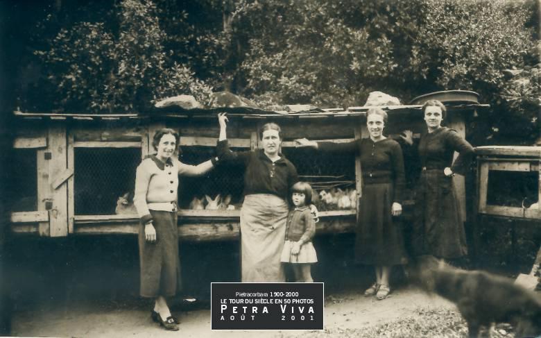 1932. Elevage de lapins à l'Oreta. Les trois sœurs Defendini sont sur leur 31 pour cette photo plutôt rustique. Seule Gabrielle Boraschi est en tenue de travail. S'occuper des lapins est un travail domestique comme un autre, il est celui des femmes et des enfants. Observez les grosses pierres qui servent à tenir les tôles du toit. Collection Paul Franceschi.