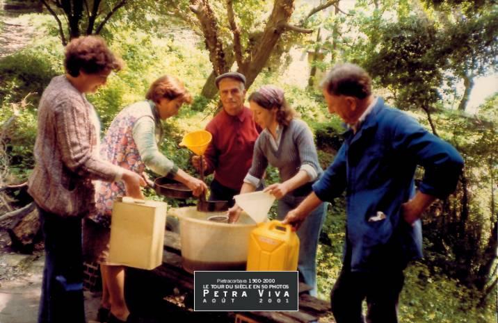 1980. Distribution d'huile d'olive à Lapedina. Après le travail, sa juste récompense : la distribution de l'huile nouvelle, fruitée à souhait et très colorée mais parfaitement naturelle ! Collection Félix Giuliani.