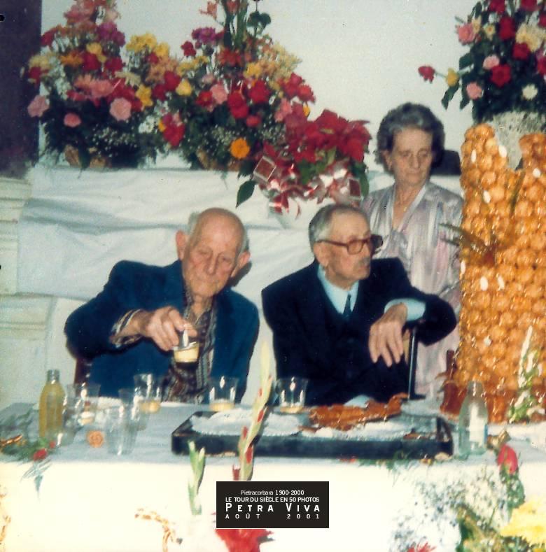 1985. Fête d'un centenaire. A eux deux ils ont 198 ans ! Théodore Dominici a 100 ans et l'impressionnante pièce-montée - deux fois plus de choux que d'années ! - est pour lui. A ses côtés, Vincent Graziani, 98 ans, trinque à la longévité de son frère d'âge mais lui ne parviendra pas à l'égaler. Collection Dédé Sinigaglia.